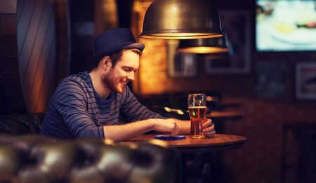 alcoholic man: people and technology concept - happy man with smartphone drinking beer and reading message at bar or pub Stock Photo