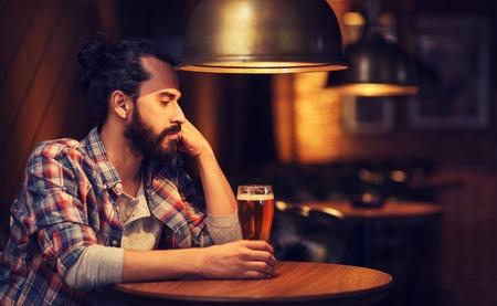 soledad: la gente, la soledad, el alcohol y el concepto de estilo de vida - hombre infeliz con la cerveza barba beber en el bar o pub Foto de archivo