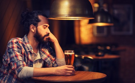 unhappy people: people, loneliness, alcohol and lifestyle concept - unhappy single man with beard drinking beer at bar or pub Stock Photo