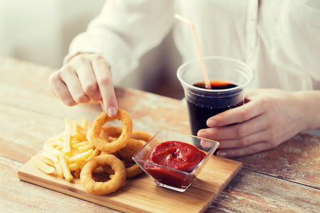 animal body part: fast food, people and unhealthy eating concept - close up of woman eating deep-fried squid rings, french fries with ketchup and drinking cola on wooden table