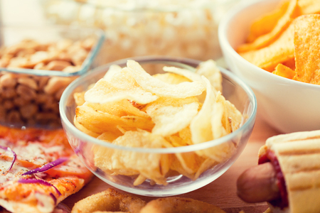 fast food, junk-food, cuisine and eating concept - close up of crunchy potato crisps in glass bowl and other snacks Stock Photo