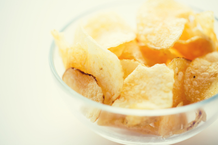 junkfood: fast food, junk-food, cuisine and eating concept - close up of crunchy potato crisps in glass bowl