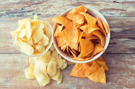 junkfood: fast food, junk-food, cuisine and eating concept - close up of potato crisps and corn nachos in bowls on table Stock Photo