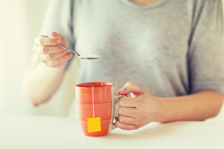 sweetening: food, junk-food, drinks and unhealthy eating concept - close up of woman adding sugar to tea cup Stock Photo
