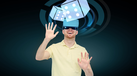 mediated: 3d technology, virtual reality, cyberspace, entertainment and people concept - happy young man with virtual reality headset or 3d glasses playing game with casino dice projection over black background