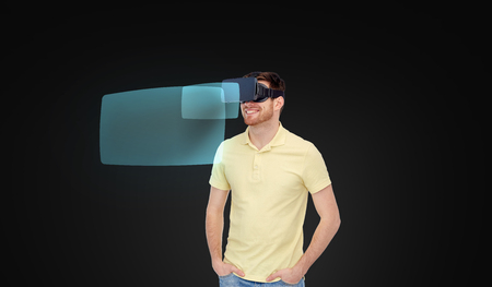 mediated: 3d technology, virtual reality, entertainment and people concept - happy young man in virtual reality headset or 3d glasses with screen projections sover black background Stock Photo
