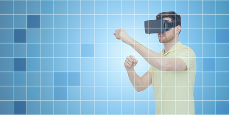 entertainment background: 3d technology, virtual reality, entertainment and people concept - young man with virtual reality headset or 3d glasses playing game and fighting over blue grid background