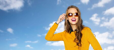 fashion clothes: people, style and fashion concept - happy young woman or teen girl in casual clothes and sunglasses over blue sky and clouds background