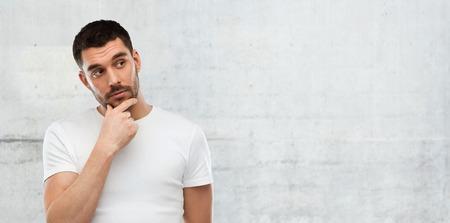 hombre pensando: duda, la expresión y el concepto de la gente - hombre de pensamiento sobre fondo gris de la pared Foto de archivo