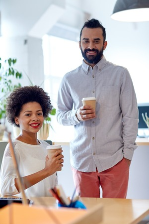 african business man: business, startup, people and drinks concept - happy latin man and african woman drinking coffee in office
