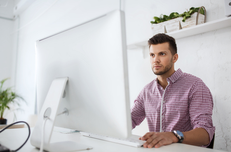 business, technology, education and people concept - young creative man or student with computer at office Stock Photo