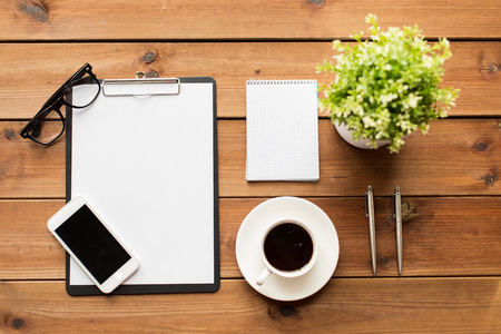 flower pot: business and technology concept - close up of smartphone, clipboard, coffee cup, eyeglasses and notepad on wooden table Stock Photo