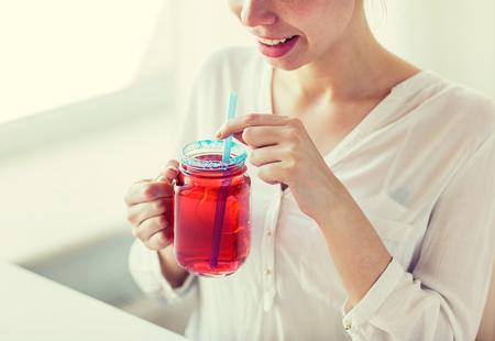 mensen, dranken en vakantieconcept - sluit omhoog van gelukkig vrouw het drinken sap van glasmok met stro thuis