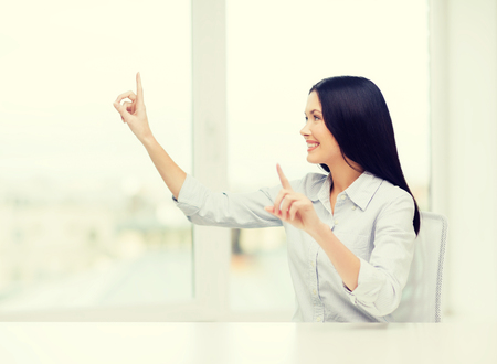 imaginary: business, education and technology concept - smiling woman pointing to something or pressing imaginary button