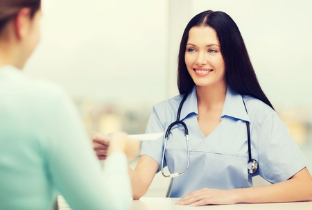 health woman: healthcare and medical concept - smiling female doctor or nurse with patient writing prescription
