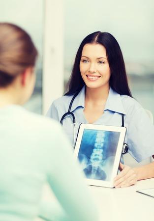 cuidado de la salud, la medicina, radiología y concepto de la tecnología - sonriente mujer médico o enfermera que muestra x-ray en el PC tableta