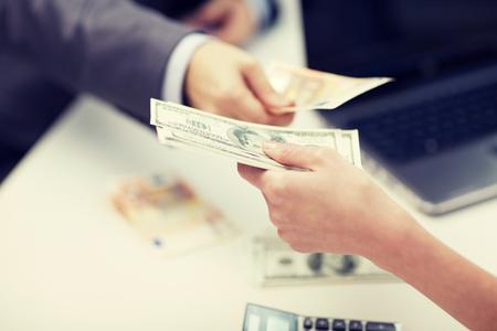 concepto de finanzas, moneda, tipo de cambio, y la gente de negocios - cerca de las manos masculinas y femeninas que den o el intercambio de dinero en la oficina