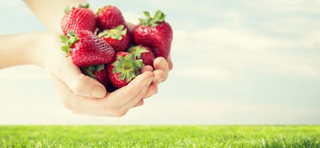 healthy eating, dieting, vegetarian food and people concept - close up of woman hands holding ripe strawberries over grass and blue sky background Stock Photo