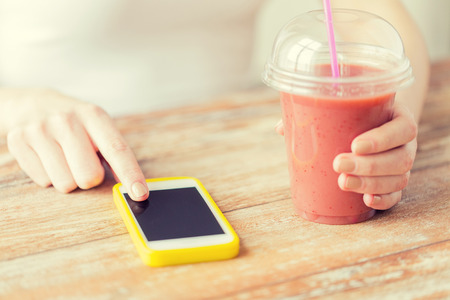 health woman: healthy eating, diet, technology and people concept - close up of woman with smartphone and cup of smoothie sitting at table