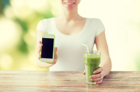 mobile app: healthy eating, diet, detox, technology and people concept - close up of woman with smartphone green juice sitting at wooden table over green natural background