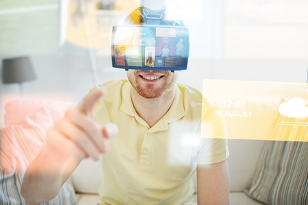 mediated: technology, multimedia, mass media, entertainment and people concept - happy young man in virtual reality headset or 3d glasses with media or web applications at home Stock Photo