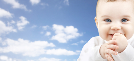 baby face: babyhood, childhood and people concept - happy baby face over blue sky background Stock Photo