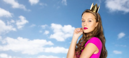 people, holidays and fashion concept - young woman or teen girl in pink dress and princess crown over blue sky and clouds background