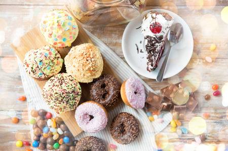 junks: junk food, culinary, baking and eating concept - close up of glazed donuts, cakes and chocolate sweets on table Stock Photo