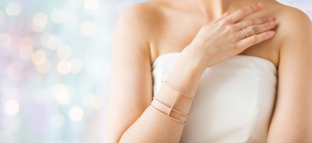 bride bangle: glamour, beauty, jewelry and luxury concept - close up of beautiful woman with golden ring and bracelet over holidays lights background