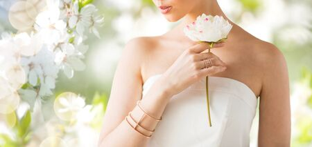 bride bangle: glamour, beauty, jewelry and luxury concept - close up of beautiful woman with golden ring and bracelet holding flower over natural spring cherry blossom