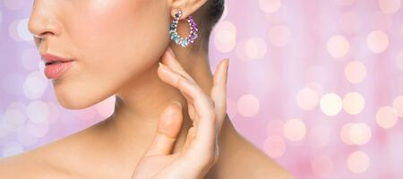 glamour luxury: glamour, beauty, jewelry and luxury concept - close up of beautiful woman face with earring over pink holidays lights background