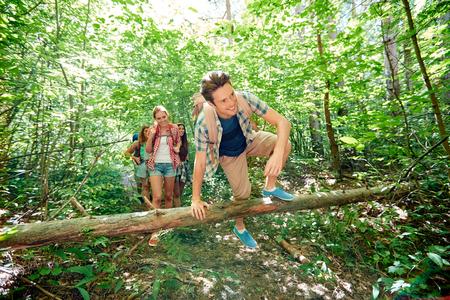 abenteuer, reise, tourismus, wandern und Personen-Konzept - Gruppe von lächelnden Freunden zu Fuß mit Rucksack in Holz Standard-Bild