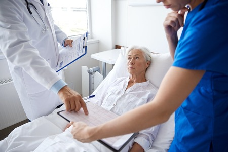 patient care: medicine, age, health care and people concept - doctor and nurse with clipboards visiting senior patient woman at hospital ward Stock Photo
