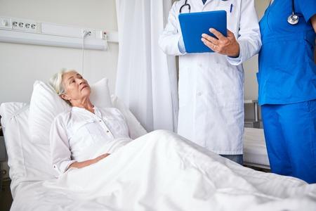 concetto di medicina, l'età, l'assistenza sanitaria e la gente - medico e infermiere con computer tablet pc visitare anziano donna paziente al reparto ospedaliero