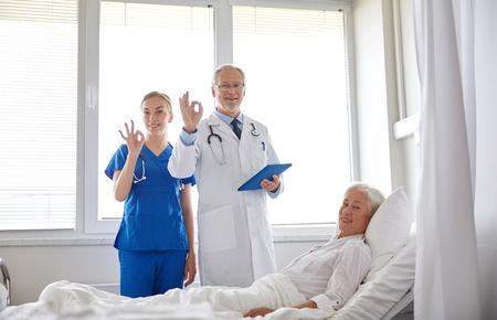 buena salud: la medicina, la edad, la salud y las personas concepto - médico y la enfermera con el ordenador Tablet PC visitar mujer mayor paciente y muestra la muestra aceptable en sala de hospital