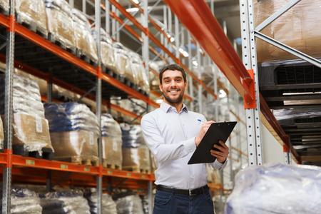 al por mayor, logística, comercial, exportación y concepto de la gente - hombre o gerente con el portapapeles comprobación de mercancías en el almacén