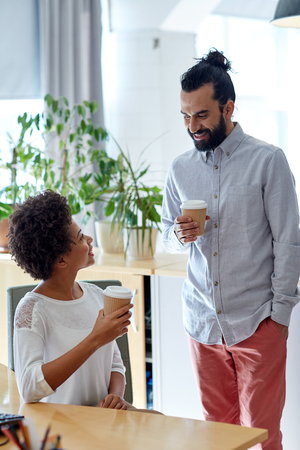 african business man: business, startup, people and drinks concept - happy latin man and african woman drinking coffee and talking in office Stock Photo