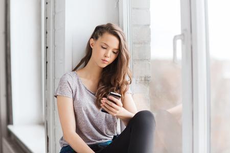 人・技術・十代の若者たちのコンセプト - スマート フォン、テキスト メッセージと窓辺に座っている悲しい不幸なかなり 10 代少女