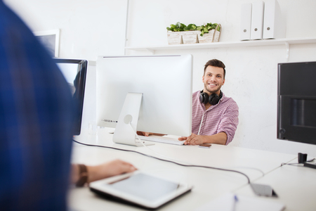 office man: business, startup, education, technology and people concept - happy creative man or student with headphones and computer at office Stock Photo
