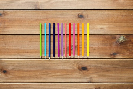 wooden color: art, color, drawing, creativity and object concept - close up of crayons or color pencils on wooden table