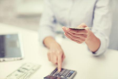 ahorro, las finanzas, la economía, la tecnología y el concepto de la gente - cerca de la mujer contando el dinero con la calculadora