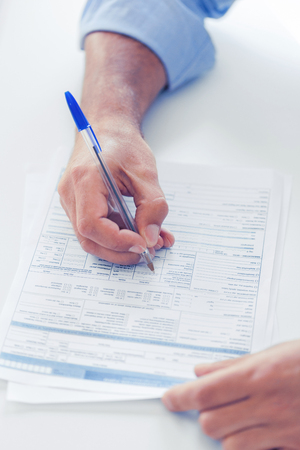 municipal utilities: business, tax, office, school and education concept - man filling a form
