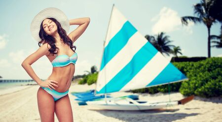 seashores: people, summer vacation, tourism and travel concept - happy young woman in bikini swimsuit and sun hat over sailing boats on tropical beach background