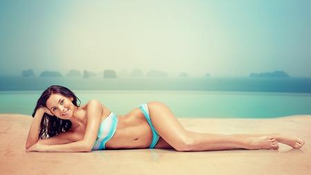 traje de baño: gente, moda, traje de baño, verano y el concepto de viaje - mujer joven feliz acostado y el bronceado en traje de baño bikini