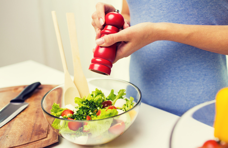 seasoning: healthy eating, vegetarian food, cooking and people concept - close up of young woman seasoning vegetable salad with salt or pepper at home Stock Photo