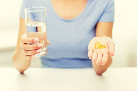home health care: healthy eating, medicine, health care, food supplements and people concept - close up of woman hands holding pills or fish oil capsules and water glass at home