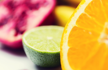 healthy eating, food, fruits and diet concept - close up of fresh juicy orange and lime Stock Photo