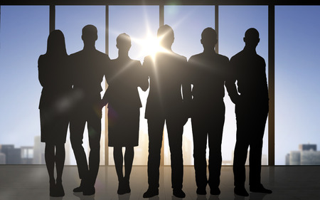 business team: business, teamwork and people concept - business people silhouettes over office background