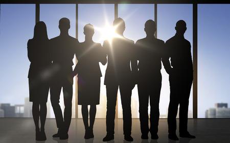 Unternehmen, Teamarbeit und Menschen Konzept - Geschäftsleute Silhouetten über Büro Hintergrund