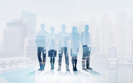 Unternehmen, Teamarbeit und Menschen Konzept - Geschäftsleute Silhouetten über Stadt Hintergrund mit Doppel-Exposition Wirkung